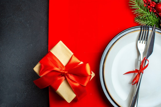 Połowa ujęcia tła xsmas z zestawem sztućców z czerwoną wstążką na talerzu obiadowym akcesoria do dekoracji gałązki jodły obok prezentu na czerwonej serwetce