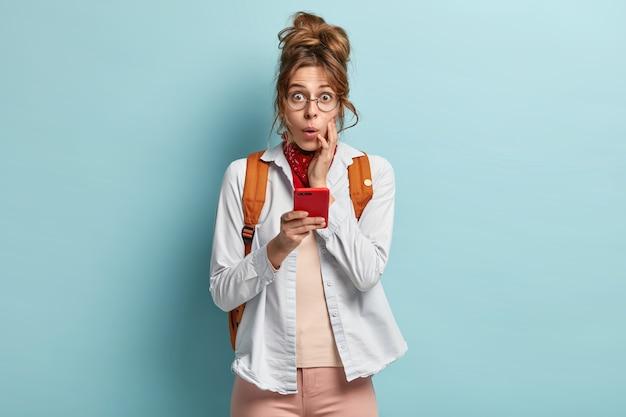 Połowa ujęcie młodej kobiety pod wrażeniem z przerażoną miną, trzymającej nowoczesny telefon komórkowy, podróżującej autostopem