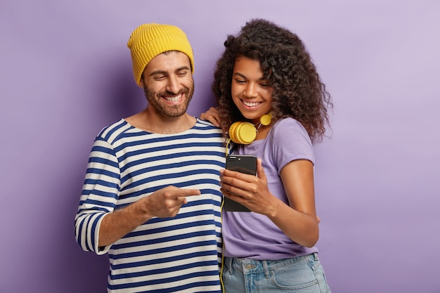 Połowa ujęcie wesołej dziewczyny i chłopaka ogląda zabawne treści wideo na smartfonie, stań blisko, miej wesołe miny, podłączone do bezprzewodowego internetu