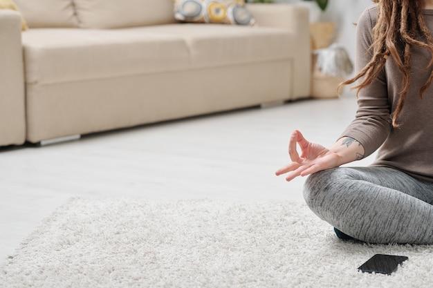 Połowa wysportowanej dziewczyny w odzieży sportowej siedzi w pozie lotosu na podłodze podczas ćwiczeń jogi w domu