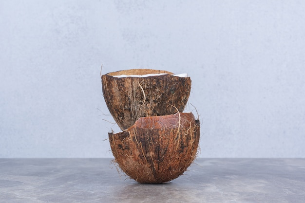 Połowę pokrojonych świeżych kokosów na kamiennym stole.
