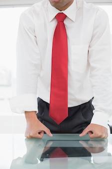 Połowie sekcji dobrze ubrany biznesmen z zaciśniętymi pięściami na biurku