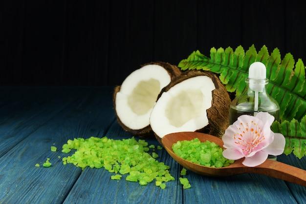 Połówka kokosowa z solą morską i zieloną łyżką z kwiatkiem i butelką