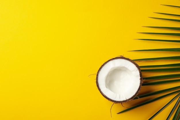 Połówka kokosowy i palmowy liść na kolorze żółtym, odgórny widok
