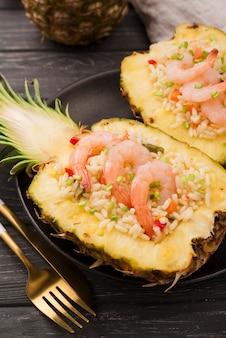 Połówki ananasa z krewetkami i złotymi sztućcami