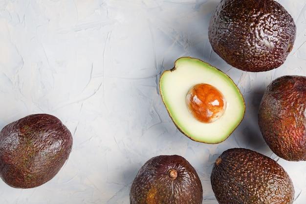 Połówki awokado z całymi owocami hass na powierzchni szarego betonu, kamienia lub łupka. widok z góry z miejsca na kopię.