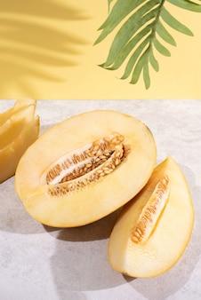Połówki dojrzałego soczystego melona na żółtym tle w słońcu, letnie jedzenie.