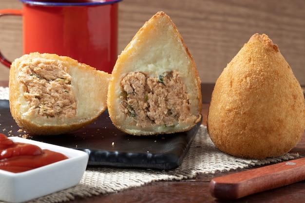 Połówki i cała brazylijska przekąska coxinha z kurczaka z keczupem.