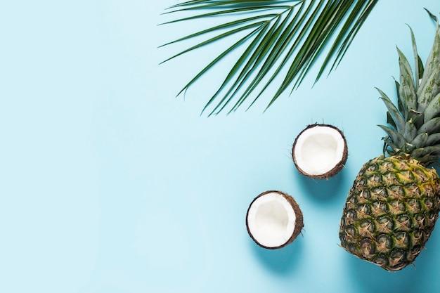 Połówki kokosa, ananasa i liści palmowych na niebiesko