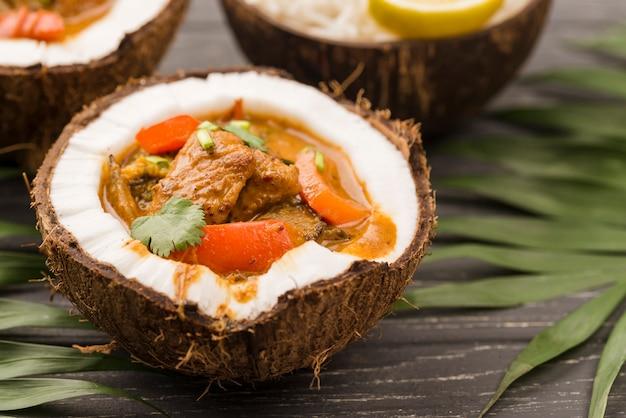 Połówki kokosa wypełnione gulaszem z bliska