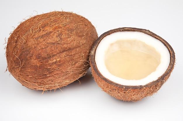 Połówki kokosa z kokosem, mlekiem i miąższem na białym tle