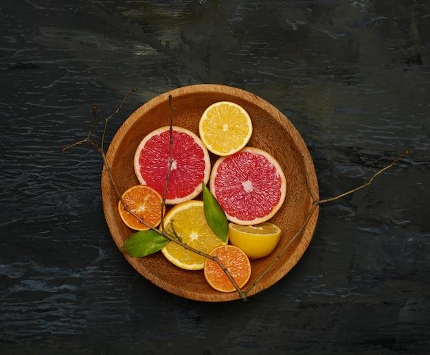 Połówki owoców cytrusowych grejpfrutów na drewnianym talerzu