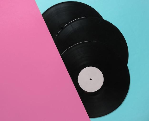 Połówki płyt winylowych na niebieskim różowym tle. albumy muzyczne retro, lata 70. widok z góry