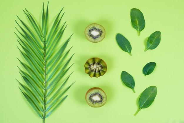 Połówki świeżego zielonego kiwi i zieleni liście na zielonym tle