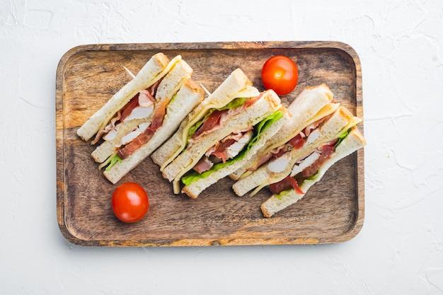 Połówki świeżych kanapek klubowych, na białym tle, widok z góry