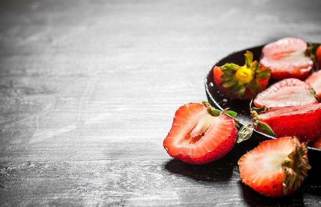 Połówki truskawek w starym talerzu. na czarnym drewnianym stole.