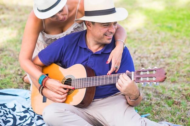 Połowy dorosłego człowieka grającego na gitarze, podczas gdy żona obejmując się od tyłu, siedząc w ogrodzie. kochająca para spędzająca wolny czas podczas wakacji. szczęśliwa para spędza wolny czas grając na gitarze na świeżym powietrzu