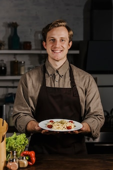 Połowy strzału kucharz trzyma talerz z makaronem
