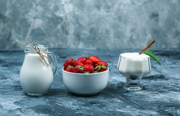Połóż miskę truskawek na czerwonym ręczniku w kratkę, dzbanek mleka i szklaną miskę jogurtu na granatowej marmurowej powierzchni. wolne miejsce w poziomie na tekst