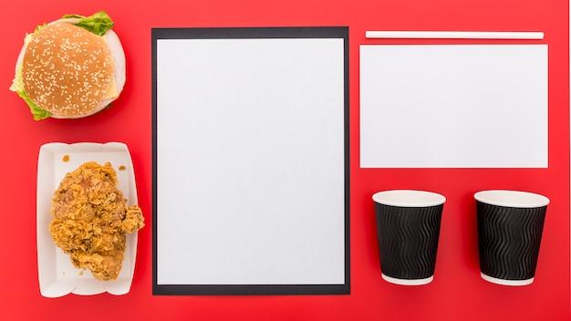 Połóż na płasko czysty papier menu z filiżankami i burgerem