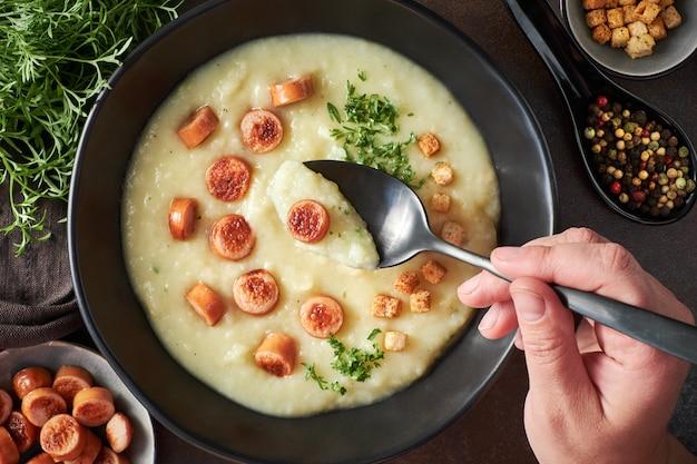 Połóż na płasko domowy krem z ziemniaków z grzankami, smażone kiełbaski wiedeńskie i zieloną kolendrę