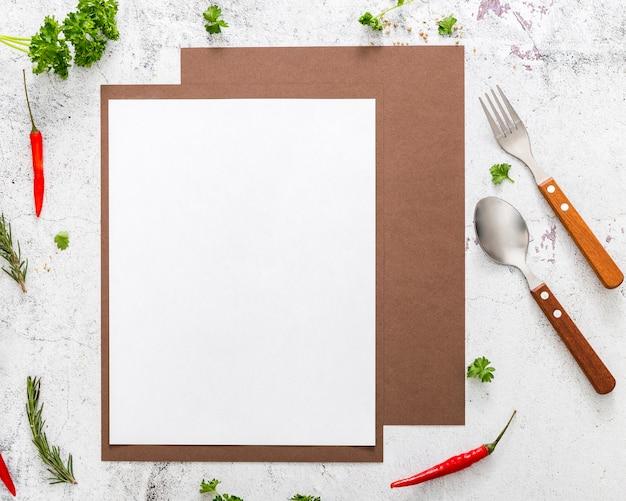 Połóż na płasko pusty papier menu z papryczkami chili i sztućcami