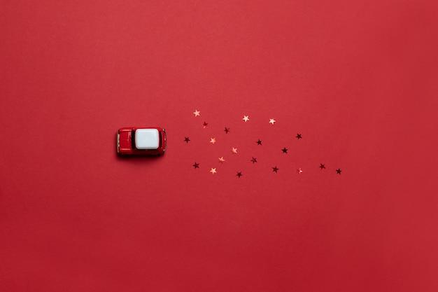 Połóż na płasko świąteczną kompozycję kart z czerwonym modelem dziecięcej zabawki samochodowej z brokatowymi cukierkami na czerwonym nasyconym tle