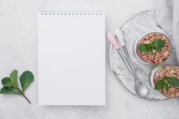 Połóż na płasko szklanki jogurtu ze zbożem i notatnikiem