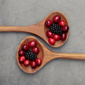 Połóż na płasko żurawinę i jagody w drewnianej łyżce