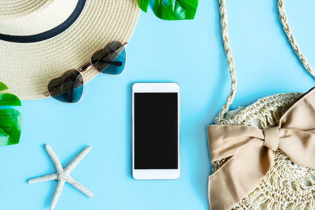 Połóż płasko letnią torbę, okulary przeciwsłoneczne, kapelusz plażowy, smartfon i liście palmowe, widok z góry i miejsce. koncepcja lato.