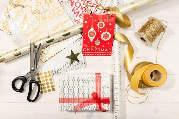 Połóż płasko prezenty świąteczne, papier dekoracyjny, wstążki i nożyczki.