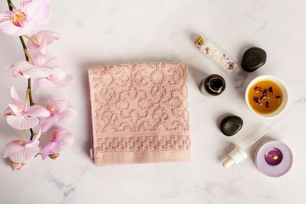 Połóż płasko przedmioty spa z ręcznikiem i kwiatami