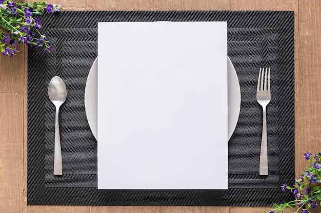 Połóż płasko pusty papier menu na talerzu z kwiatami i sztućcami