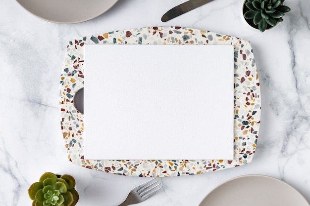 Połóż płasko pusty papier menu na talerzu ze sukulentami
