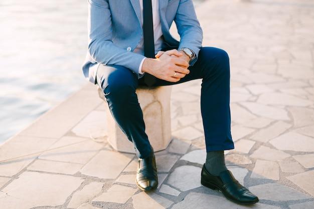 Półportret mężczyzny w szarym garniturze siedzącego na nasypie w pobliżu wody