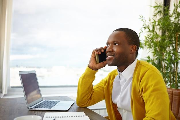Półprofilowe ujęcie przystojnego stylowego afroamerykańskiego projektanta rozmawiającego przez telefon komórkowy z klientem, omawiającego szczegóły i pomysły dotyczące projektu wnętrza domu, o inspirowanym wyglądzie, siedzącego przy oknie