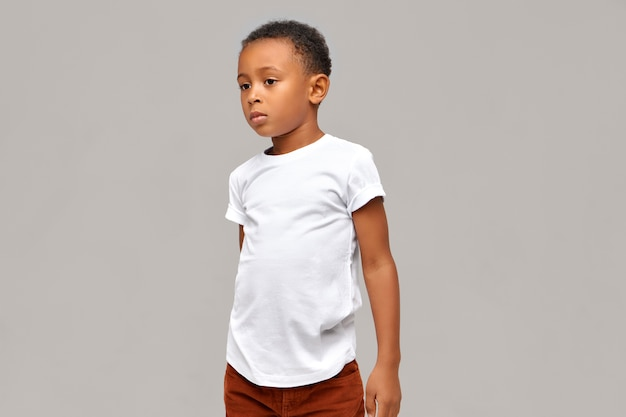 Półprofilowe zdjęcie niedbale ubranego afrykańskiego chłopca w białej koszulce o spokojnym, pewnym siebie wyrazie twarzy, pozuje odizolowane od pustej ściany z miejscem na kopię dla twoich informacji
