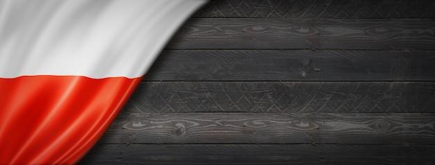 Polska flaga na czarnej ścianie z drewna. poziomy baner panoramiczny.