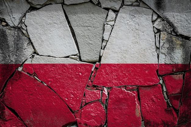 Polska flaga narodowa przedstawiająca w kolorach farb na starym kamiennym murze. flaga transparent na tle rozbitej ściany.