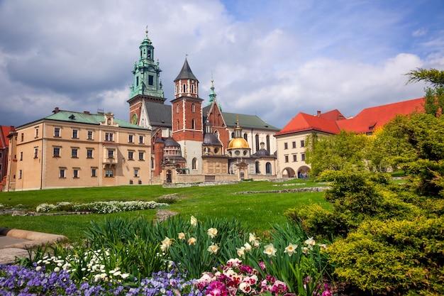 Polska. kraków. zamek królewski na wawelu. kwitnący park i kopuły katedry na zachmurzonym niebie
