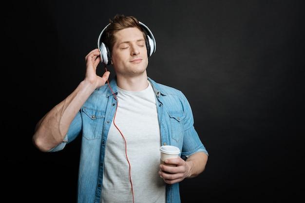 Polubowny, spokojny, przystojny mężczyzna trzyma filiżankę kawy i słucha piosenek, używając słuchawek i stojąc przed czarną ścianą