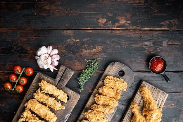 Południowe kawałki kurczaka smażone na ciemnym drewnianym stole, widok z góry.