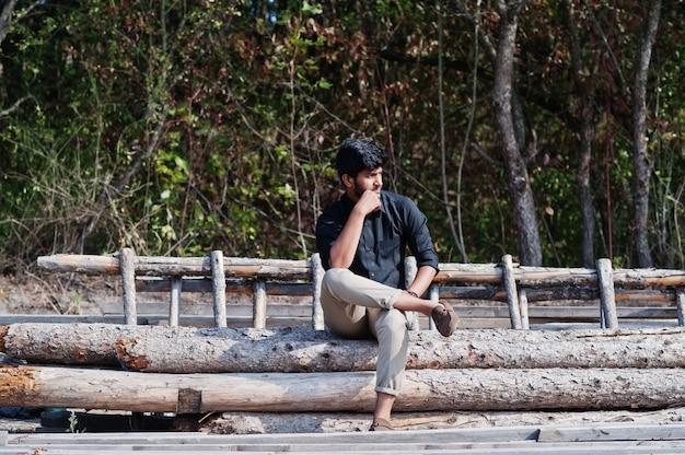 Południowo-azjatycki agronom średniorolny obsiadanie na drewnach przy gospodarstwem rolnym. koncepcja produkcji rolnej.