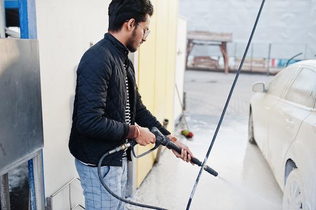 Południowo azjatycki mężczyzna lub indyjski samiec myje jego białego transport na myjni samochodowej.