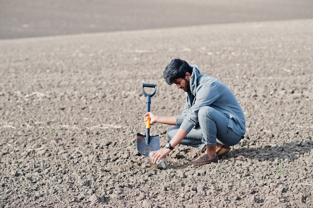 Południowoazjatycki agronom rolnik z łopatą sprawdza czarnej ziemi. koncepcja produkcji rolnej.
