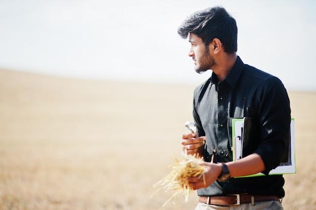 Południowoazjatycki agronomu rolnik sprawdza pszenicznego pola gospodarstwo rolne. koncepcja produkcji rolnej.