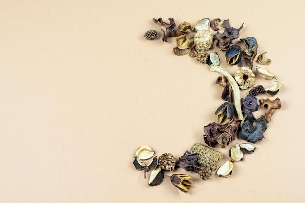 Półwianek z suszonych kwiatów i liści wanilii na beżowo-pastelowym tle papieru.