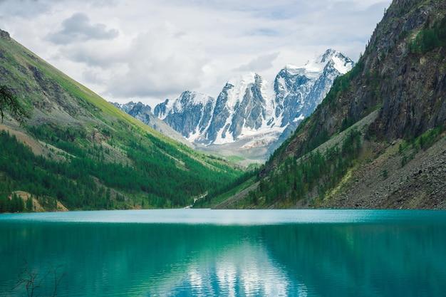 Połysk wody w górskim jeziorze w górach. cudowne gigantyczne zaśnieżone góry. creek wypływa z lodowca. biały śnieg na grzbiecie. niesamowity klimatyczny krajobraz majestatycznej przyrody ałtaju.