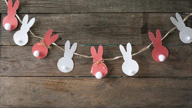 Pom pom easter bunny craft. zajączek ozdoba papieru wyciąć tło. świąteczna girlanda diy z kolorowych królików
