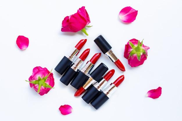 Pomadki z kwiatem róży na białym tle. piękny makijaż